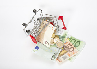 Shopping concept image. Miniature shopping cart filled with cash. European bank notes and coins. Trolley is broken and money fallen out.