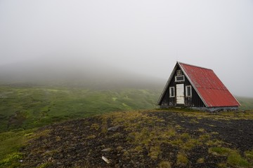 A cabin on a hill shrouded in mist.