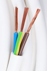 Electrical power cable close up. IEC standard color code. Cross-section with cable jacket, wire insulations in brown, blue and yellow-green color with flexible stranded copper wires. Macro photo.