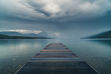 Wall Mural - Dock overlooking a calm overcast lake.
