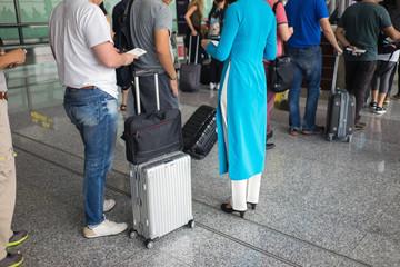 Queue of people in Noi Bai airport, Vietnam. Focus on female staff wearing Vietnamese long dress Ao Dai