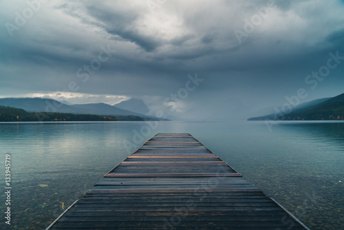 Wall mural Dock overlooking a calm overcast lake.