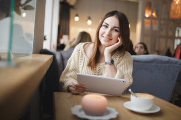 Cute woman using tablet pc in a cafe