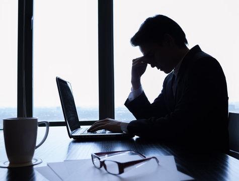 Sad and stressed businessman at work.