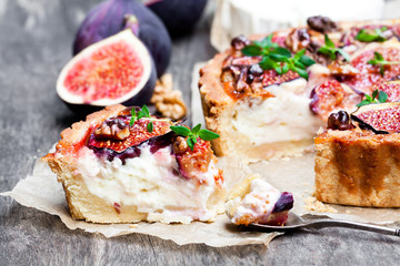 Delicious  tart with fresh figs and goat cheese on rustic wooden