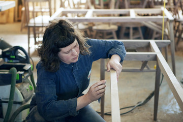 Female carpenter examining wooden frame at workshop