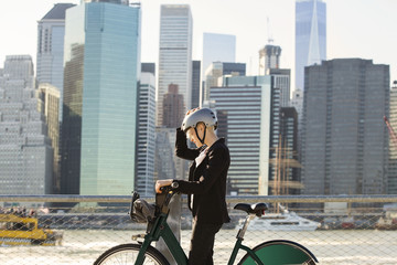 Side view of woman wearing helmet standing with bicycle by river and buildings