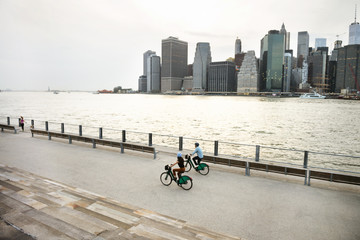 High angle view of couple cycling on promenade in city against sky