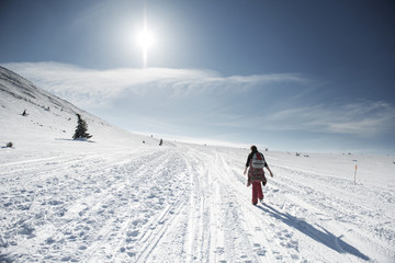 Rear view of woman walking on snow covered field against sky on sunny day