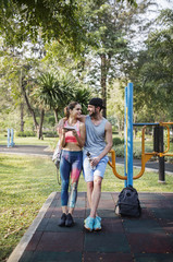 Front view of happy couple leaning over exercise equipment at park