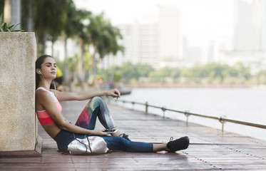 Woman listening music and relaxing on wooden walkway at park