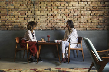 Smiling businesswomen talking while sitting at table in hotel lobby