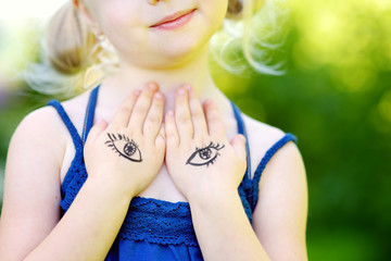 Cute little girl covering her chest with her hands on summer day