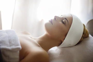 Relaxed woman lying on massage table in spa