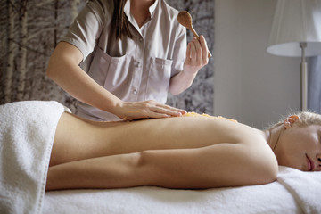 Midsection of massage therapist applying medicine on woman's back in spa