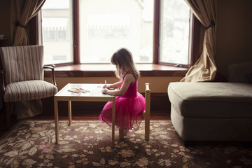 Side view of girl drawing at table in living room