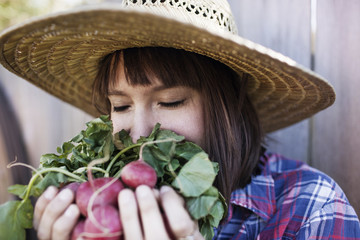 Young woman smelling radishes at organic farm