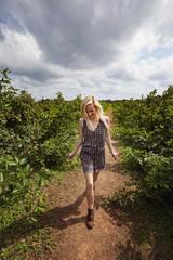 Happy female farmer walking on field against cloudy sky