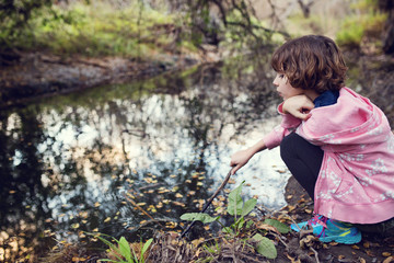 Side view of girl holding stick while sitting by stream in forest