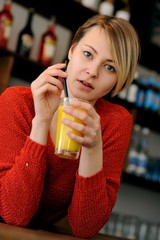 Attraktive, junge, blonde Frau mit Orangensaftglas