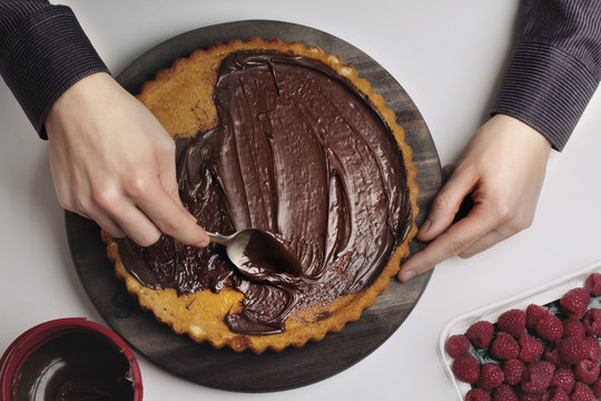Cropped image of man spreading melted chocolate on tart