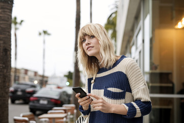 Thoughtful young woman holding smartphone by city street