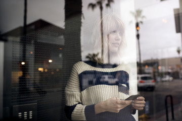 Thoughtful young woman holding smart phone seen through glass wall