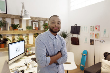 Portrait of confident male illustrator standing arms crossed in creative office