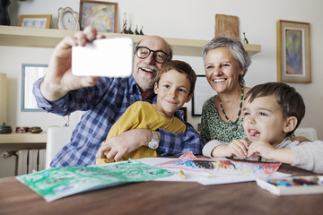 Cheerful senior man taking selfie with family at home