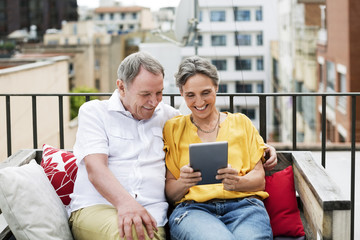 Cheerful senior couple using tablet computer while sitting on bench at terrace