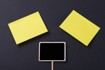 Two yellow post-its next to a square blackboard on a black background
