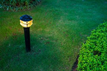 Illuminated outdoor light in apartment garden at twilight, evening.