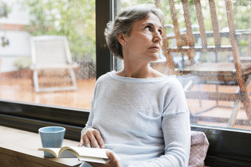 Thoughtful mature woman looking through window while holding book at home