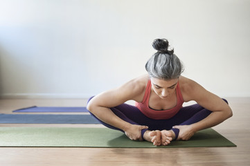 Woman practicing yoga in the gym