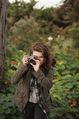 Beautiful hiker photographing through old-fashioned camera in forest