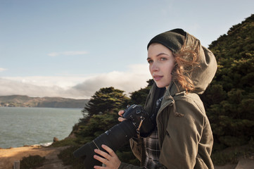 Thoughtful female photographer holding camera while standing outdoors