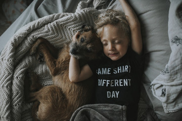 High angle view of boy sleeping with dog on bed at home