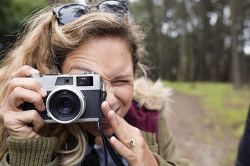 Close-up of woman photographing through camera in forest