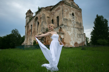 Young bride in a wedding dress posing against the backdrop of an old abandoned church