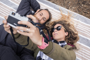Woman showing photographs to man on camera while lying on blanket in forest