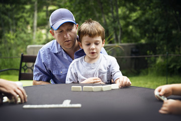 Father and son playing domino at table in backyard