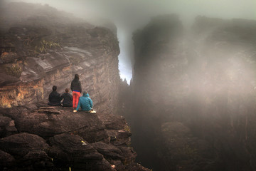 Rear view of friends sitting on rock in foggy weather