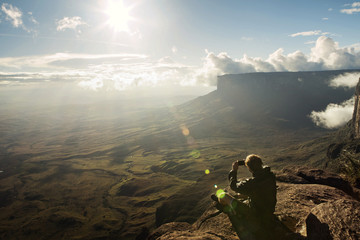 High angle view of man photographing while sitting on cliff