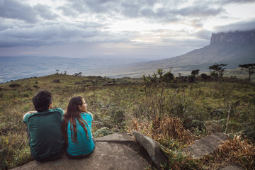 Rear view of man and woman sitting on rock against cloudy sky