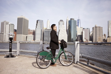 Businessman looking at view while holding bicycle from observation point