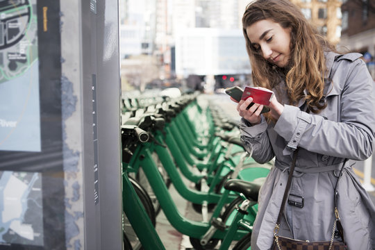 Young woman holding credit card while using smart phone by Citi Bikes at parking lot