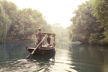 Rear view of man rowing boat on river