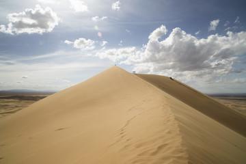 Sand dune against cloudy sky on sunny day