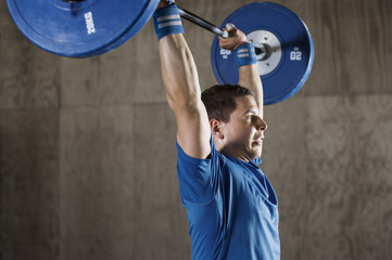 Side view of determined male athlete lifting barbell in health club