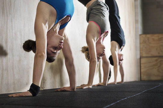 Sportswomen doing handstand exercise against wall in gym